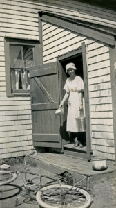 Woman at back door bicycle on ground AHM copy