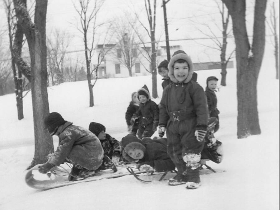 B7 - Four families  share a toboggan,  Protestant manse in background c. 1959