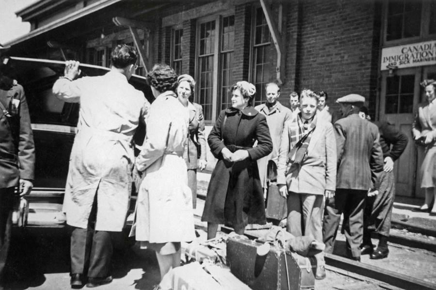 B8 - Joanne (Bekkers)  & Casey Van de Sande by suitcases, Pier 21, Halifax,  1956